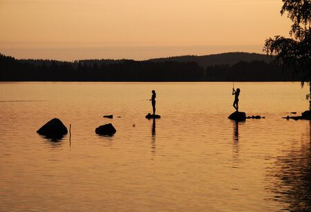 Teenage girl and boy are standing on stones and fishing rod in the big forest lake. They are photographed at sunset. photo