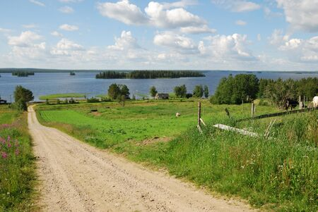 Country natural road is running between green fields and pastures.  In the background there are blue water of big forest lake and the summer sky with clouds.