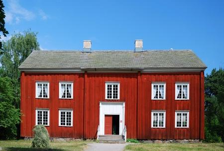 Zweistöckige Holzhaus liegt in der Scansen. Im Hintergrund sind Summer Forest und den blauen Himmel. Das Anwesen ist im neunzehnten Jahrhundert gebaut. Standard-Bild - 8483336