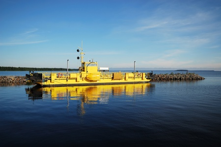 Yellow ferry is sailing in the quiet lake. There are a lot of blue water and the clear sky of Manamansalo. photo
