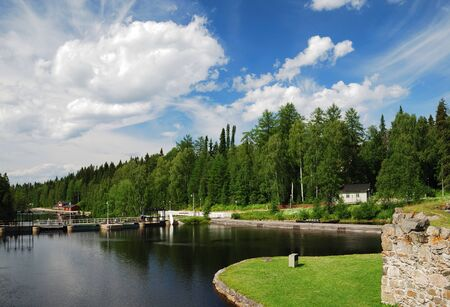 Finnish town Kajaani is photographed at lovely summer day. There are an island with ancient ruins, calm river, green forest and the fantastic sky.
