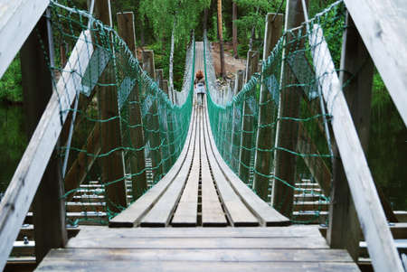 Pendant bridge is photographed with diminishing perspective. Female tourist is trekking along hiking trail of the Little Bears Ring.  photo