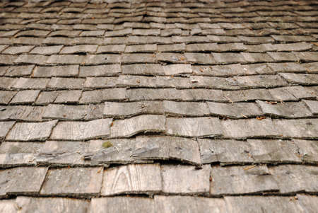 Old shingle roof is photographed closely. photo