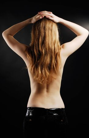 Blonde woman is standing from back in the black background. She is topless. She is wearing only black pants. She is putting her arms on her head. photo