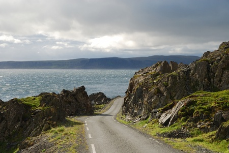 diminishing perspective: Asphalt road is running along north Norwegian coast. This is the road to Hamningberg. Highway is photographed with diminishing perspective. Stock Photo