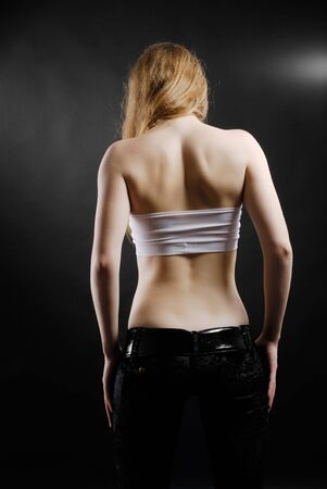 Teenage girl is standing from back in the black background. She is upset and her blond head and shoulders are hung. She is wearing a white top and black pants. She is putting arms on her hips. photo