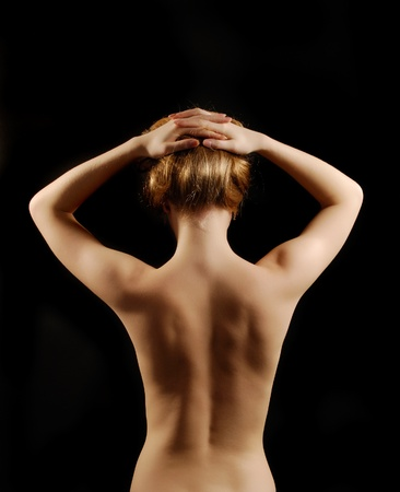 Blonde woman is standing from back in the black background. She is nude. She is putting her arms on her head and holding her fair hair.