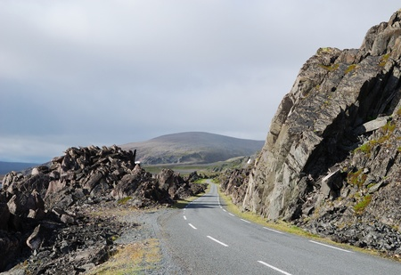 diminishing perspective: Asphalt road is meandering between among rocks of north Norwegian coast. This is the road to Hamningberg. Highway is photographed with diminishing perspective.  Stock Photo