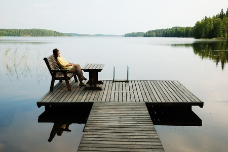 女性は木の肘掛け椅子に座っています。彼女は静かな湖の近く板敷プラットフォームで休んでいます。