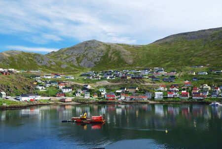 Fishing town is located on the side of blue fjord. Mageroya is photographed in summer. There are wooden houses on the green mossy hills and a lot of blue water. photo