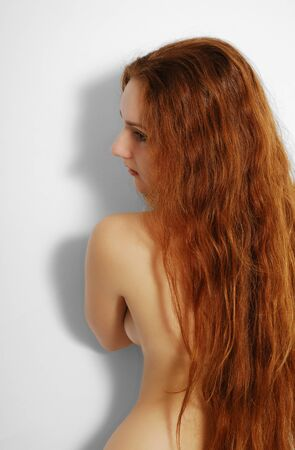A ginger woman is standing back against the white background. Her back is closed with long red hair. Her sexy body has produced shadow on the white wall. He has turned left her face.  photo
