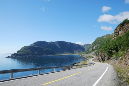 Asphalt road is meandering between blue fjord and moss mountains. Highway is photographed with diminishing perspective. Mageroya is an island in Finnmark county in the extreme north of Norway.  photo