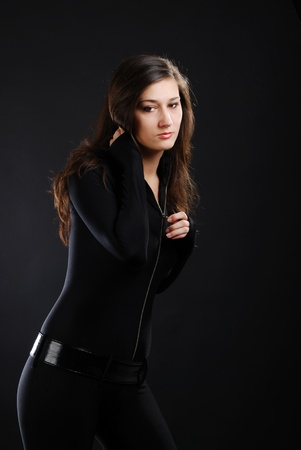 catsuit: Teenage girl is photographed in low key against the dark background. She is wearing a black cat-suit and lacquered belt. Young woman is thinking and smiling slightly. Her dark long hair are let down.