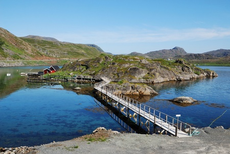 Fishing village is in the small island surrounded with blue fjord. It is connected the long bridge. Mageroya is photographed in summer. There are several wooden houses, motorboats, mossy hills and a lot of transparent water. photo