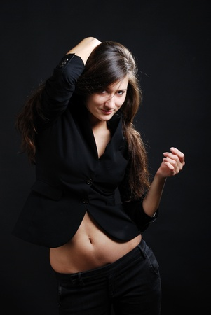 Teenage girl is photographed in low key against the dark background. Young woman is smiling and looking sullenly at camera. Her pretty belly arent covered with black jacket.