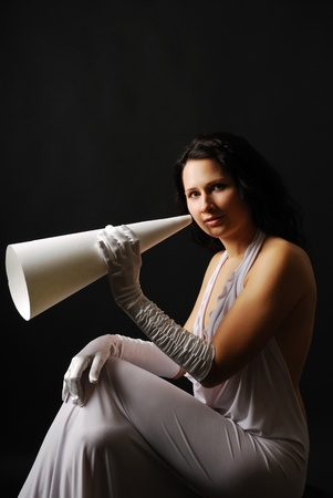 speaking trumpet: Elegant woman is sitting and holding a speaking trumpet in the black background. Young woman is looking at camera. She is wearing a white evening dress and long satin gloves. Her dark long hair are flowing. Stock Photo