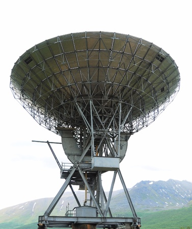 Large radio telescope is situated under green mountain. The sky is overcast.