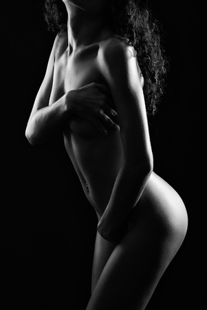Naked woman is covering the body her arms. She is photographed in low key. The photo is black-and-white. Stock Photo