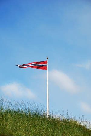 Norwegian flag is flying on the green roof against the blue sky. photo