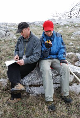 Man is examining the terrestrial map. The compass is hung on his neck. Teenage boy is orienteering by GPS. They are finding their bearings on the ground. Both hikers are sitting on a rock.