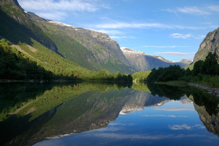 Smooth surface of clear water is reflecting the blue sky and green mountain overgrown with forest. Norwegian fjord is photographed in the summer. photo