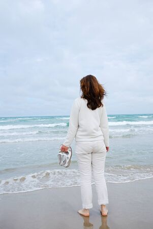 barefooted: Barefooted woman is standing on the wet sand beach. She is wearing a windcheater and jeans. She is facing the blue sea and the cloudy sky. Waves are rolling in the flat seashore.