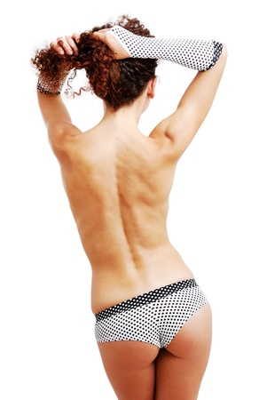sexy topless woman: Topless woman is standing back. She is lifting up her hairs with her hands. The frizzy girl is wearing polka dot shorts and gloves. Her sexy body is accentuated with erotic clothes.