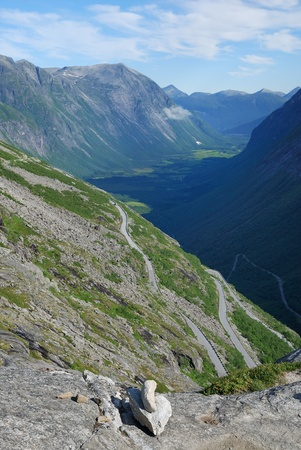meandering: Serpentine road is meandering along the flank of mountains. Famous Trollstigen is photographed against the dark ravine and ridge of Norwegian mountains.