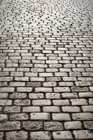 Cobblestone pavement was photographed closely with diminishing perspective. Focus is on the front cobbles.