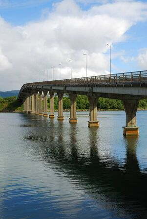 bridge footing: Long concrete highway bridge over the wide fjord. Stock Photo