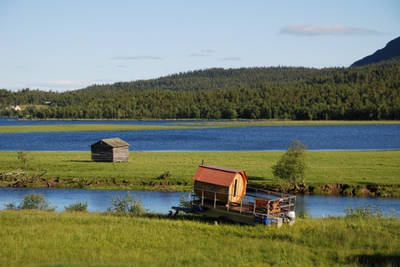 ferryboat: A small wood ferryboat is moored on the green meadow. There are a wide lake and a hill covering taiga forest. Stock Photo