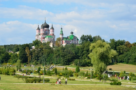 grassy plot: Majestic church towers above the large green garden. The persons are having a walk in the Feofaniya park.  Stock Photo