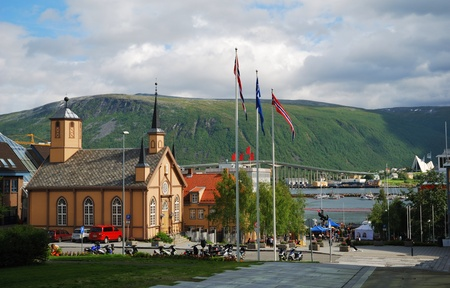 Wooden church is on the modern street of Tromso. It is photographed in sunny day.