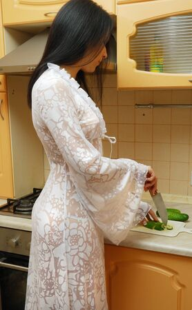 Young woman is cooking in the cosy kitchen. She is wearing a long dressing gown. photo