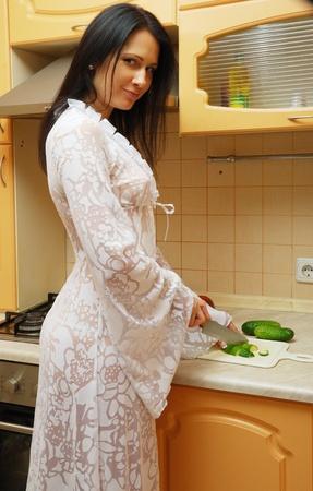 若い女性は居心地の良いキッチンで料理を。彼女は、カメラを見ています。幸せな女の子はきゅうりを切っています。彼女は長いガウンを着ています。 写真素材