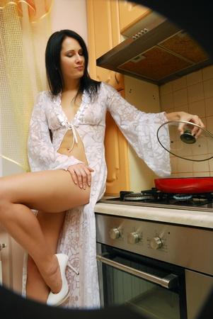 seducing: Giovane donna sta cucinando in cucina accogliente. Sta prendendo una cover di padella. Indossa un abito lungo medicazione.