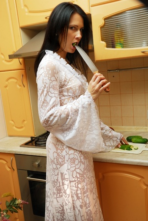 Young woman is cooking in the cosy kitchen. She is pushing a slice of cucumber into her mouth. She is wearing a long dressing gown.