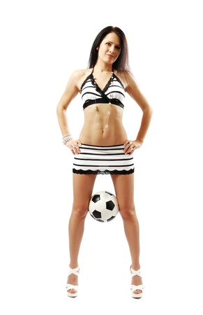 between: Sexy woman is standing and holding a football between her slim legs. She is wearing a short skirt and top. Stock Photo