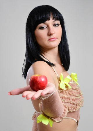 Young woman is holding out a red apple and looking at it. This fruit is on the foreground. Stock Photo - 11031207