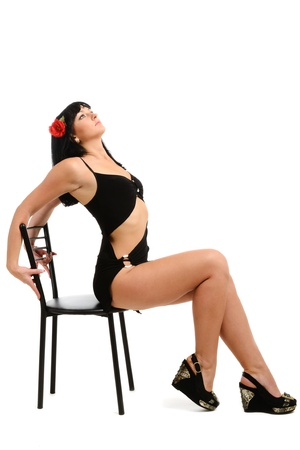 Young woman is sitting on the edge of the black chair and bending her back. She is wearing a black short dress. Red flower is in her dark long hair. Stock Photo - 11103966