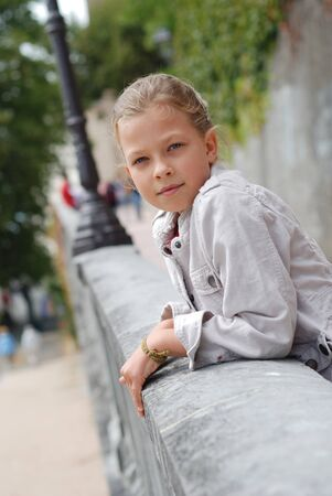 9 year old: Preteen girl is leaning on the parapet and looking calmly at the camera. She is photographed in the park.