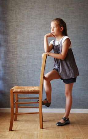 9 year old: Preteen girl is standing near the chair. She leans on the chair and looks sideways dreamily.