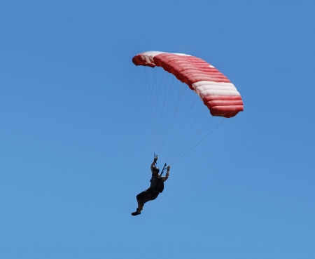 paragliding: Parachutist with red parachute is flying in the blue sky. Stock Photo