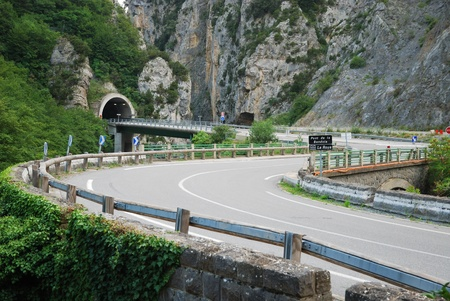 Asphalt road is twisting along sheer cliffs overgrown with lush greenery. Highway is winding through picturesque European Alps in summer.