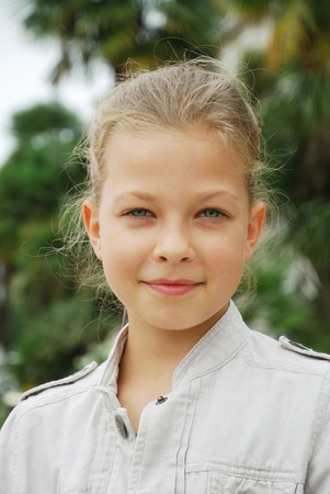 9 year old: Preteen girl is looking at the camera. She is somewhat smiling.  Stock Photo