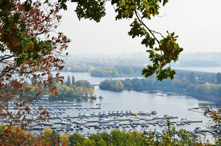 dniper: There are a lot of small piers with various boats, motorboats in the wide river. Dniper is photographed from right site of Kyiv. Stock Photo
