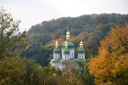 cupolas: Golden and green domes of orthodox church are photographed in the autumn park.