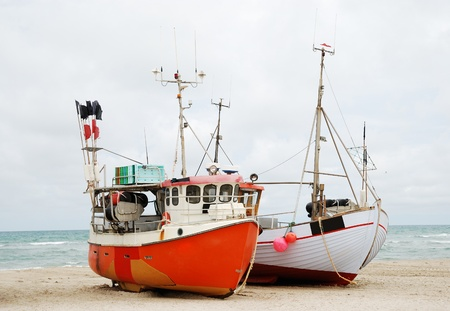 Two fishing crafts are on the sand of seacoast. The sky is overcast.