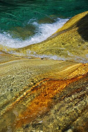 riverbed: Vibrant colored rocks are seen through the clear water flowing. The mountain river Verzaska is known for its transparent water and multicolored stones. Stock Photo