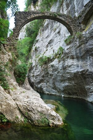 Mountainl river is flowing along sheer cliffs with lush greenery. The stone bridge is all that has remained from the natural pool. photo